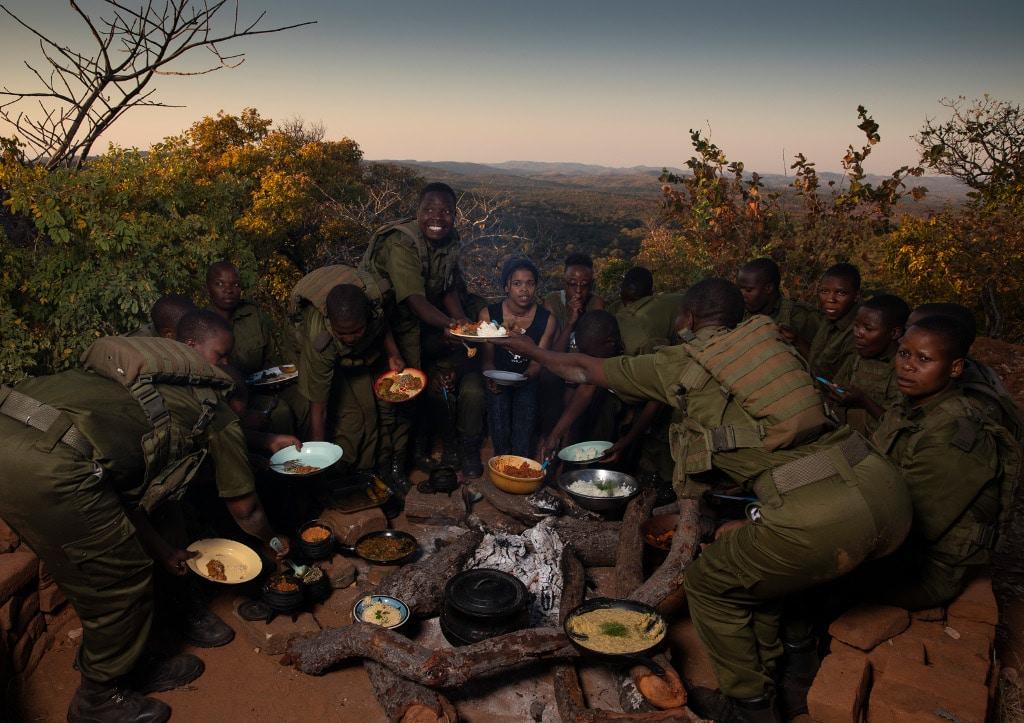 Akashinga Rangers sitting around campfire and eating