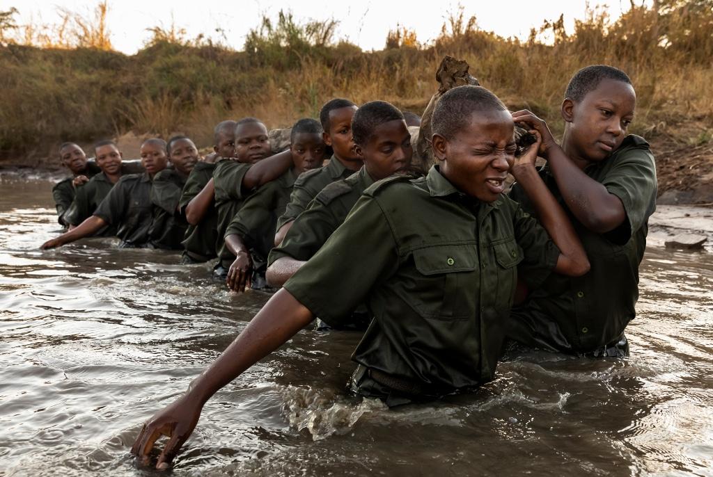 Akashinga Rangers carrying log through water